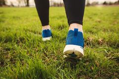 Athletic pair of legs running on grass royalty free stock photo
