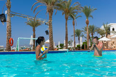 Athletic pair playing volleyball in the swimming pool. At the hotel on a sunny summer day Royalty Free Stock Image