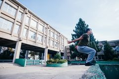 Athletic Parkour guy doing backflip and tricks while jumping off and over a concrete wall.  stock image