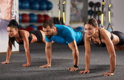 Athletic people doing crossfit training. With trx straps Royalty Free Stock Image