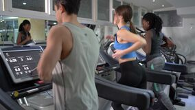 Athletic people jogging on treadmills in a gym