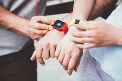Athletic people sharing workout data from their smartwatches. Sharing sports performance. Athletic and sporty couple looking at their smartwatches and sharing Royalty Free Stock Image