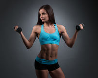 Athletic Pretty Woman Lifting Two Dumbbells Stock Photo