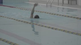 Sporty swimmer hardly working out in indoor empty pool swimming across track. Healthy lifestyle. Sports and recreation. Athletic professional swimmer hardly stock video footage