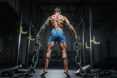 Athletic pumped man bodybuilder with chain in gym. Back view stock photo
