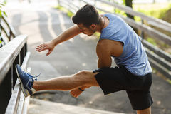 Athletic runner doing stretching exercise, preparing for morning workout in the park. Young man doing stretching exercises in a park on a wooden bridge Royalty Free Stock Photography