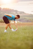 Athletic runner doing stretching exercise. Preparing for running in the nature with the city in background. Healthy lifestyle Stock Photos