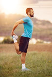 Athletic runner doing stretching exercise. Preparing for running in the nature with the city in background. Healthy lifestyle Royalty Free Stock Images