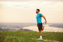 Athletic runner doing stretching exercise. Preparing for running in the nature with the city in background. Healthy lifestyle Royalty Free Stock Photos