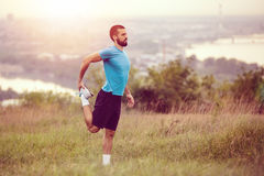Athletic runner doing stretching exercise. Preparing for running in the nature with the city in background. Healthy lifestyle Stock Images