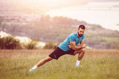 Athletic runner doing stretching exercise Stock Images