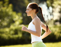 Athletic Runner Training in a park for Marathon. Fitness Girl Ru Stock Image