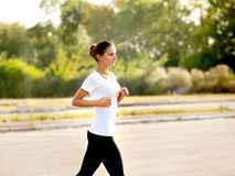 Athletic Runner Training in a park for Marathon. Fitness Girl Ru Royalty Free Stock Images