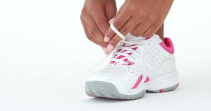 Athletic runner tying up her shoe laces. Close up view of an athletic runner tying up her shoe laces stock video