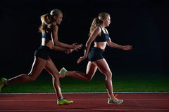 Athletic runners passing baton in relay race. Woman athletic runners passing baton in relay race stock image