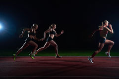 Athletic runners passing baton in relay race. Woman athletic runners passing baton in relay race royalty free stock photos
