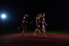 Athletic runners passing baton in relay race. Woman athletic runners passing baton in relay race royalty free stock image
