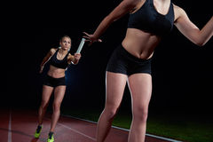 Athletic runners passing baton in relay race Stock Images