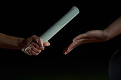 Athletic runners passing baton in relay race Stock Photo