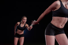 Athletic runners passing baton in relay race. Woman athletic runners passing baton in relay race Royalty Free Stock Images