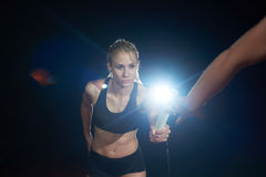 Athletic runners passing baton in relay race. Woman athletic runners passing baton in relay race Royalty Free Stock Photo