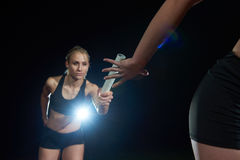 Athletic runners passing baton in relay race. Woman athletic runners passing baton in relay race Stock Images