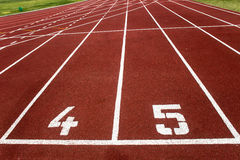 Athletics 100 Meter Start Line. Athletics one hundred meter starting line  at lanes four and five, with the first twenty meters of white marked track lanes in Royalty Free Stock Images