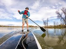 Athletic senior man on paddleboard stock photos
