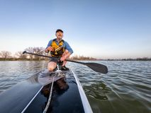Athletic senior man on paddleboard. Athletic senior man on a stand up paddleboard enjoing sunset lover a calm lake in Colorado, bow view royalty free stock photos