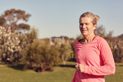 Athletic senior woman running outdoors in sporty top Royalty Free Stock Photos