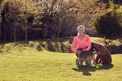Athletic senior woman smiling in a park with her dogs Royalty Free Stock Image