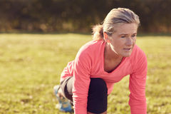 Athletic senior woman warming up for exercise and looking focuse Stock Photos