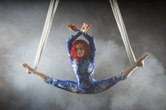 Athletic aerial circus artist with redhead in blue costume dancing in the air with balance royalty free stock photos