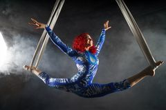 Athletic aerial circus artist with redhead in blue costume dancing in the air with balance stock photos