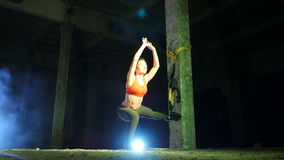 Athletic, sexy woman performs exercises with fitness trx system, TRX suspension straps. At night, in light smoke, fog. In light of multicolored searchlights stock video footage