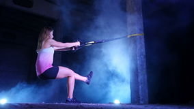 Athletic, sexy woman performs exercises with fitness trx system, TRX suspension straps. At night, in light smoke, fog. In light of multicolored searchlights stock footage