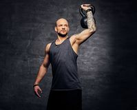 Sporty shaved head tattooed male doing shoulder workout with the Kettlebell. Athletic shaved head tattooed male doing shoulder workout with the Kettlebell Royalty Free Stock Images