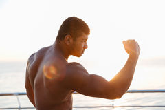 Athletic shirtless african sportsman training outdoors and showing biceps Stock Photo