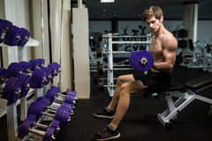 Athletic shirtless young male fitness model holds the dumbbell with light in gym Stock Photos