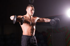 Athletic shirtless young male fitness model holds the dumbbells. Royalty Free Stock Image
