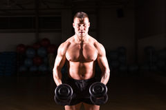 Athletic shirtless young male fitness model holds the dumbbells. Stock Photo