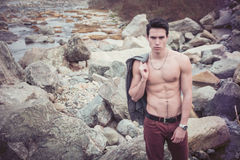 Athletic shirtless young man outdoor at river or water stream Royalty Free Stock Photos