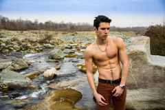 Athletic shirtless young man outdoor at river or water stream Royalty Free Stock Image