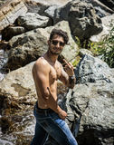 Athletic shirtless young man outdoor at river or water stream Stock Photography
