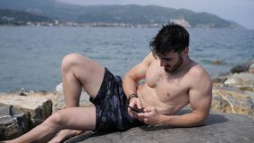Man at the seaside using cell phone to type message. Athletic shirtless young man at the seaside using cell phone to type message while looking at the sea and stock video