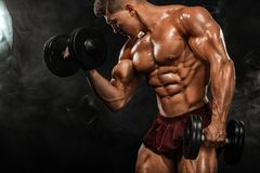 Brutal strong muscular bodybuilder athletic man pumping up muscles with dumbbell on black background. Workout royalty free stock photography