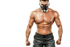 Brutal strong muscular bodybuilder athletic man pumping up muscles in training mask on white background. Workout stock images