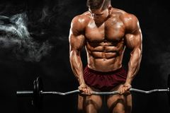 Brutal strong muscular bodybuilder athletic man pumping up muscles with barbell on black background. Workout royalty free stock image