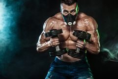 Muscular young fitness sports man, bodybuilder in training mask. Workout with dumbbell in fitness gym Stock Photos