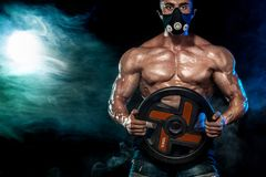 Muscular young fitness sports man in training mask. Workout with dumbbell in fitness gym. Copy space for sport nutrition ads. Royalty Free Stock Photography